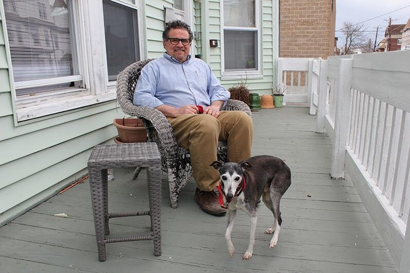 man on porch with dog